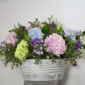 Cubo de zinc con flores variadas