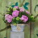 Cubo de zinc y flores en tonos rosas